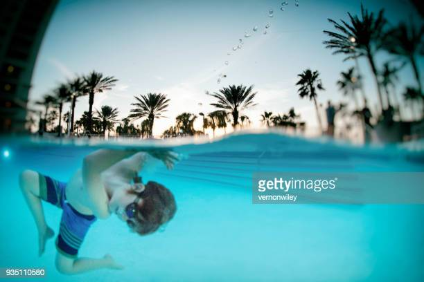 child playing underwater in a beautiful resort pool - clearwater florida stock pictures, royalty-free photos & images