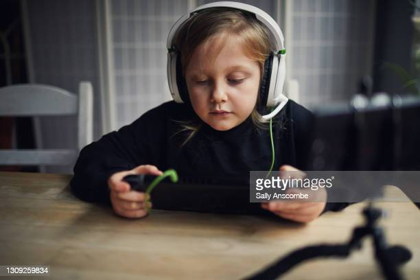 child playing video games online with friends - sally anscombe stock pictures, royalty-free photos & images