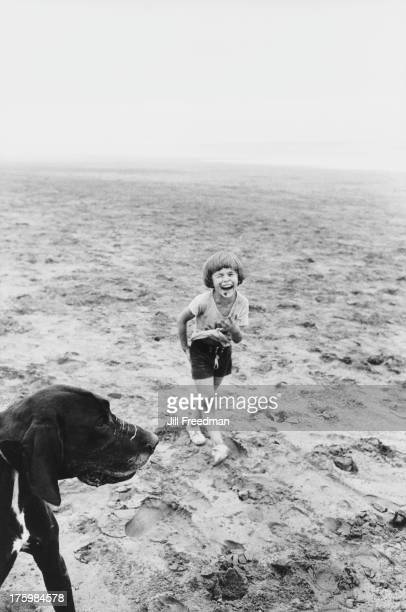 A child playing with a dog on a beach in Morocco 1975