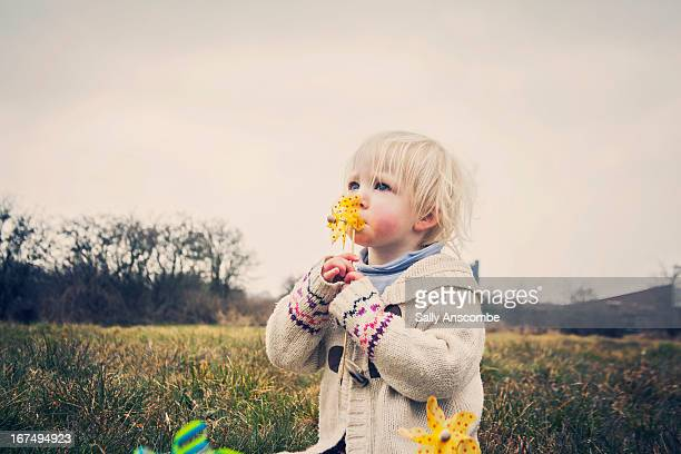 Child playing with a toy windmill