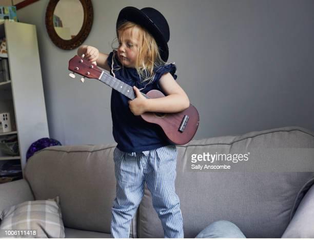 child playing with a ukulele - ukulele stock pictures, royalty-free photos & images