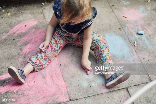child playing with chalk - britain playgrounds stock pictures, royalty-free photos & images