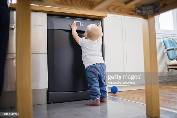 Child playing with dishwasher while parents cooking