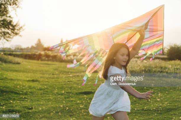 Child playing with kite in the meadow