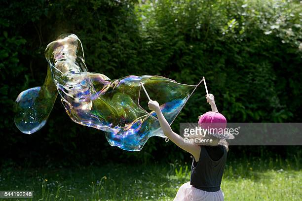 Child playing with large bubbles
