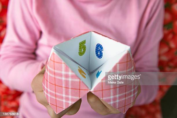child playing with paper fortune teller