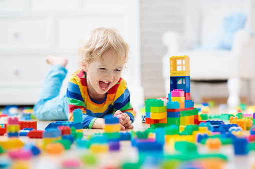 Child playing with toy blocks. Toys for kids. 1009591886