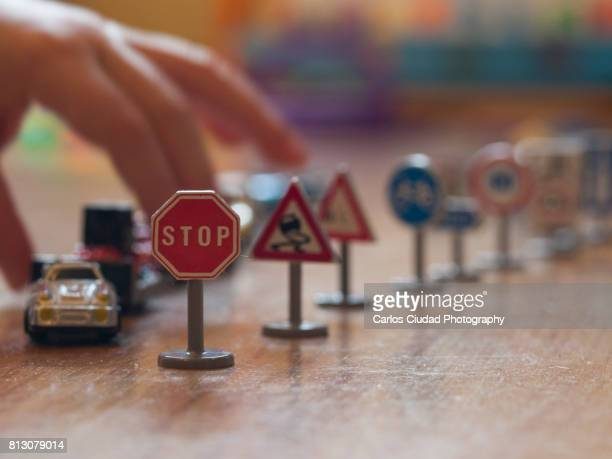 Child playing with toy cars and traffic signals on wooden floor