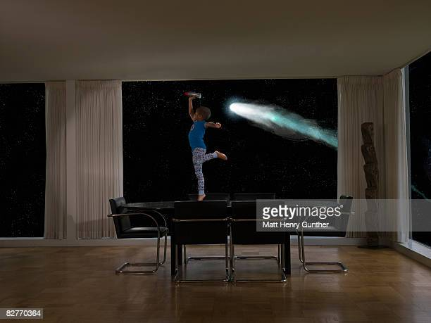 child playing with toy rocket in front of comet