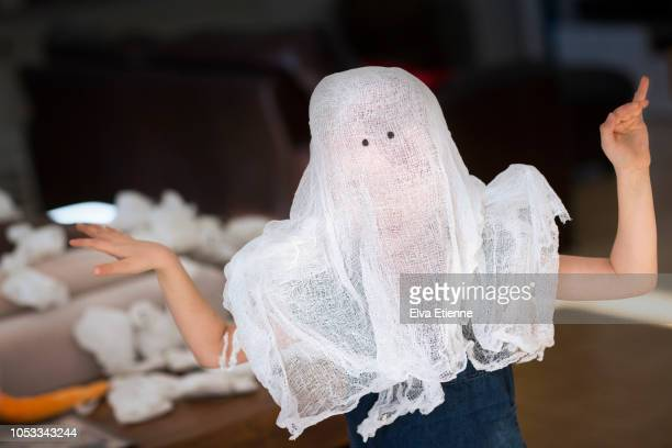 child playing with white netted cloth 'ghost' over head - ghost player foto e immagini stock
