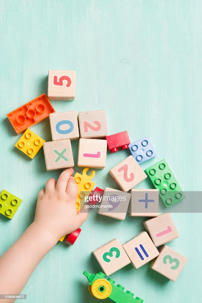 Child playing with wooden cubes with numbers and colorful toy bricks on a turquoise wooden background. Toddler learning numbers. Hand of a child taking toys. : Stock Photo