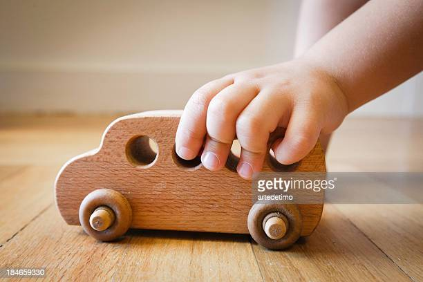 Child playing with wooden toy bus on wooden floor