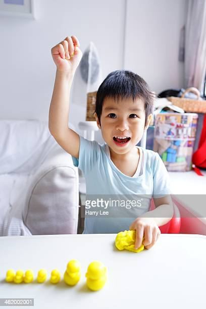 Child playing with yellow clay raising right hand
