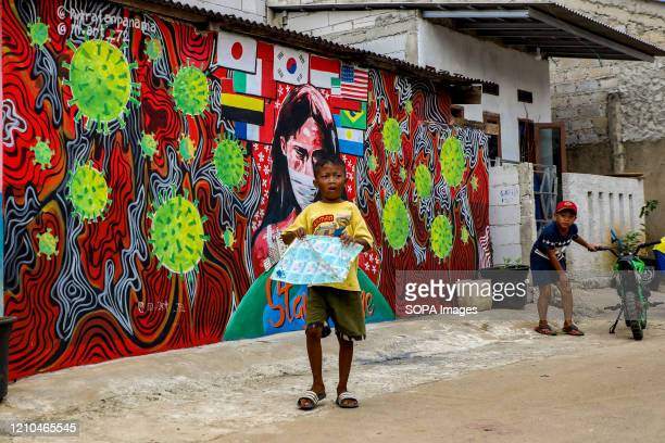 Child plays a kite near a coronavirus awareness graffiti during a lockdown. Indonesian local artists drew murals on the walls of the houses for the...