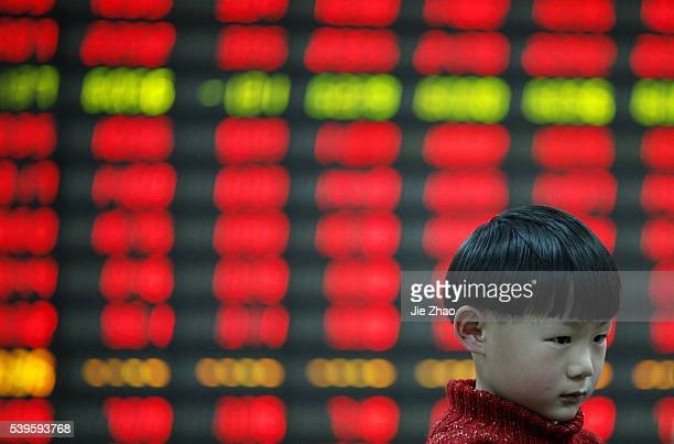 A child plays at a stock exchange in Huaibei Anhui province China on 10th April 2015 The Shanghai Composite Index climbed back above the 4000 level...