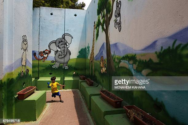 A child plays at kindergarten surrounded by decorated concrete blast walls designed to protect from rocket and mortar fire on June 24 in the southern...