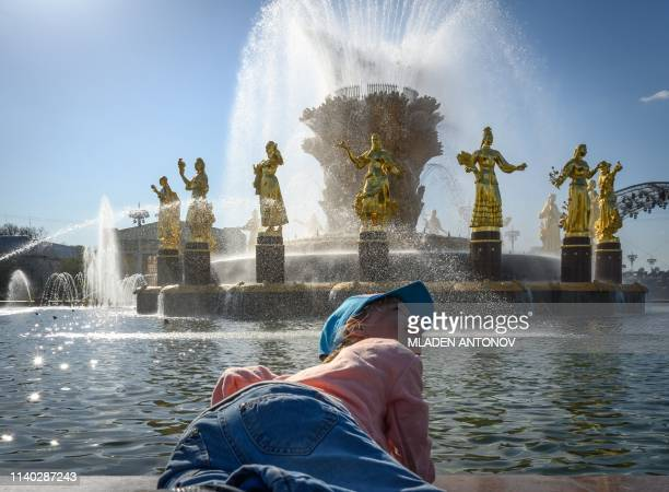 A child plays at the Friendship of Nations fountain at VDNKh on the day of its reopening following restoration in Moscow on April 30 2019 The...