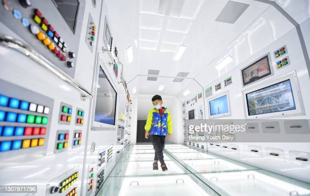 Child plays during an interactive technological exhibition on the development of China's manned space program at China Science and Technology Museum...