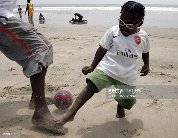 A child plays football with his father at Accra's beach on February 6 on the eve of the African Cup semifinal football match between Ghana and...