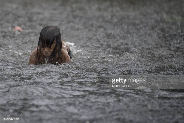 Child plays in a flooded street caused by a sudden heavy rain in Manila on July 7, 2018. - Health officials have said that the surge in leptospirosis...