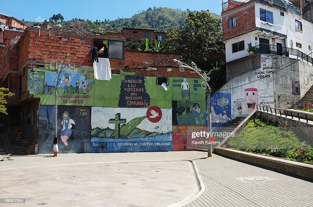 A child plays in front of murals depicting troubled times and present days in the slums, in the urban spaces constructed near Spain Library (Biblioteca Espana) built for the cultural and social transformation of the city built on the hill in the midst of slums on January 5, 2013 in Medellin, Colombia. The notorious slums of Medellin have gone through urban and educational projects to improve the quality of life for its residence.
