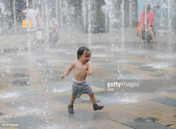 A child plays in the music fountain at Sanlitun on July 12 2017 in Beijing China The dog days of summer started from July 12 in China