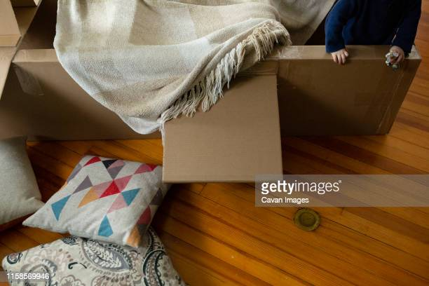 Child plays indoors in airplane made of cardboard covered with blanket