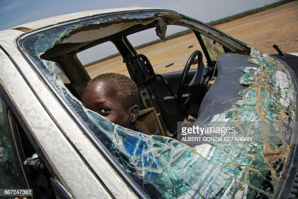 TOPSHOT A child plays inside a destroyed vehicle in the opposition controlled town of Thonyor in Leer county on April 11 2017 At least 16 civilians...