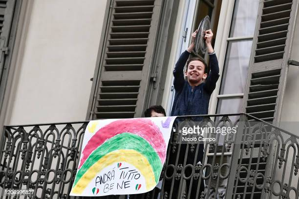 Child plays lids of pots from balcony of his home where there is a banner reading 'Everything will be fine' in the neighborhood San Salvario during a...