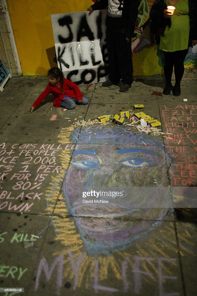 A child plays near a chalk portrait of Ezell Ford, a 25-year-old mentally ill black man, on the sidewalk near the site where he was shot and killed by two LAPD officers in August, on December 29, 2014 in Los Angeles, California. The long-awaited autopsy report, which was put on a security hold at the request of police and ordered by L.A. Mayor Eric Garcetti to be made public before the end of 2014, was released December 29.
