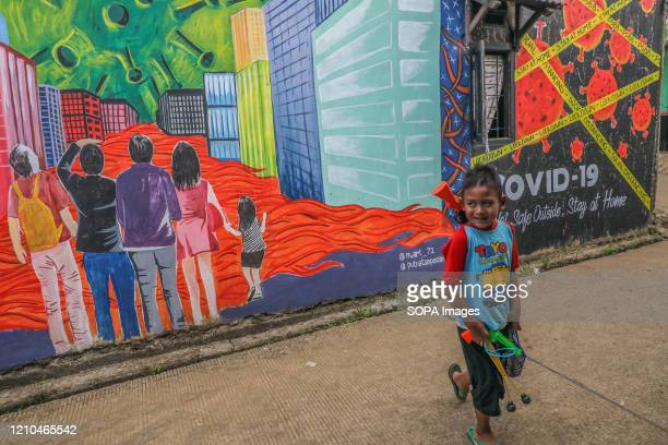 Child plays near a coronavirus awareness graffiti during a lockdown. Indonesian local artists drew murals on the walls of the houses for the...