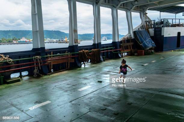 A child plays on a half empty ferry to Bali crossing the Bali Straits from Ketapang in the background to Gilimanuk in west Bali
