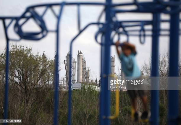 Child plays on a playground in front of a refinery in Houston, Texas, U.S., on Sunday, March 8, 2020. Houston has been purposefully going green for...