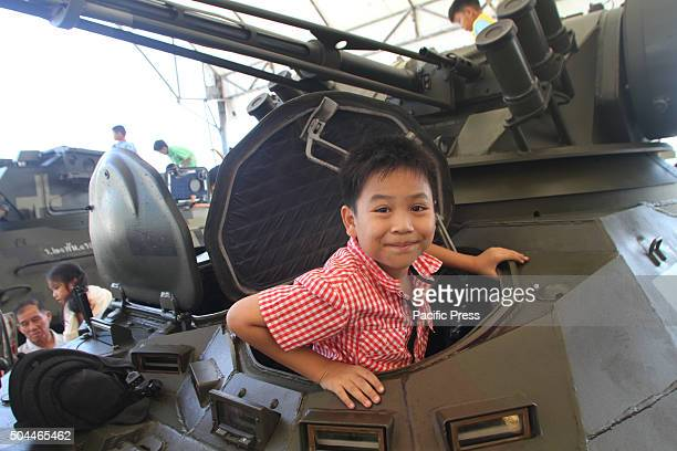 A child plays on a tank during the National Children's Day at the Horse Brigade Bangkok Weapons such as tanks troop transport artillery guns...