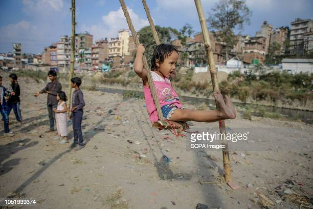 A child plays on a traditional swing locally known as ëpingí during the Hindu festival Dashain Dashain festival is one of the biggest religious...