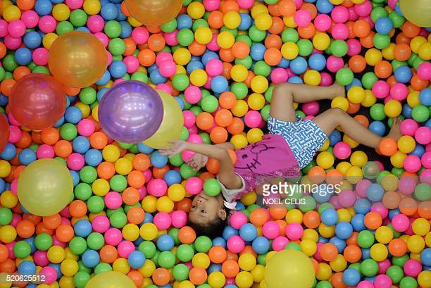 A child plays on a trampoline filled with balls and balloon at a mall Manila on April 12 2016 / AFP / NOEL CELIS