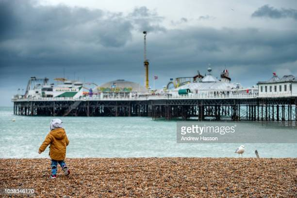 A child plays on the beach in front of Brighton Pier in wet weather on September 23 2018 in Brighton England Despite better weather being predicted...