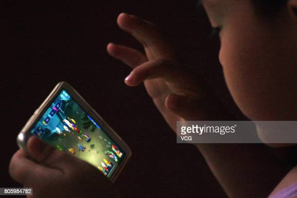 A child plays online mobile game on July 2 2017 in Dezhou Shandong Province of China China's Tencent will restrict each account's daily playtime of...