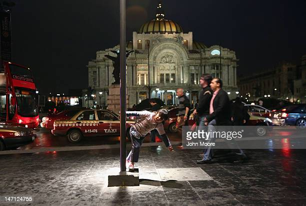A child plays while waiting for her mother to finish work in front of the Palacio de Bellas Artes as people walk home following a political...