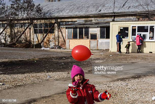 Child plays with a balloon as migrants and refugees wait for a bus at a transit camp in the southern Serbian town of Presevo on January 9, 2016. More...