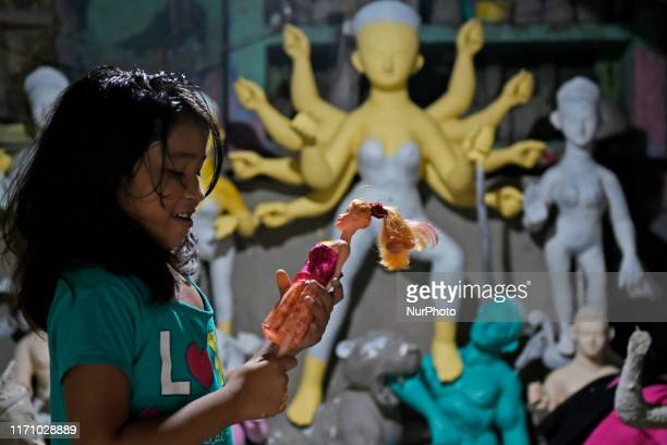 A child plays with a doll inside a Durga idol making workshop in Kolkata India 25 September 2019 The event commemorates the slaying of a demon king...
