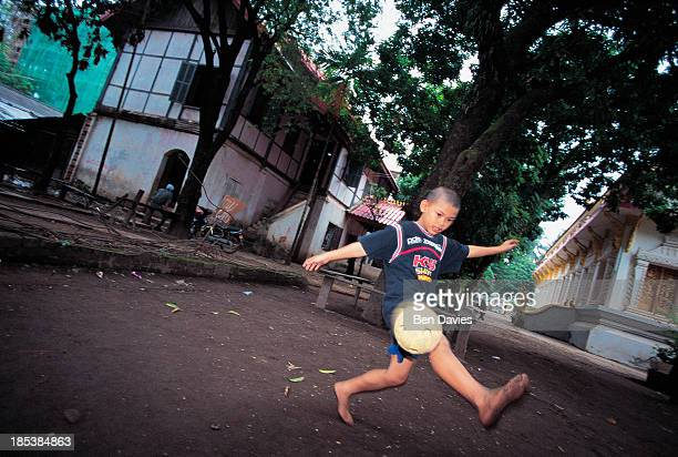 A child plays with a football inside the compound at Wat Hai Sok in Vientiane the sleepy capital of Laos The city still boasts plenty of fine old...