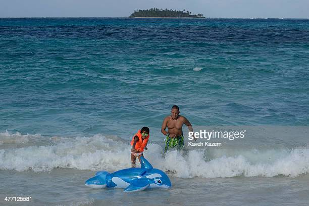 A child plays with a plastic dolphin at the beach in front of Johnny Cay coral islet located 15 km to the north on January 24 2014 in San Andres...