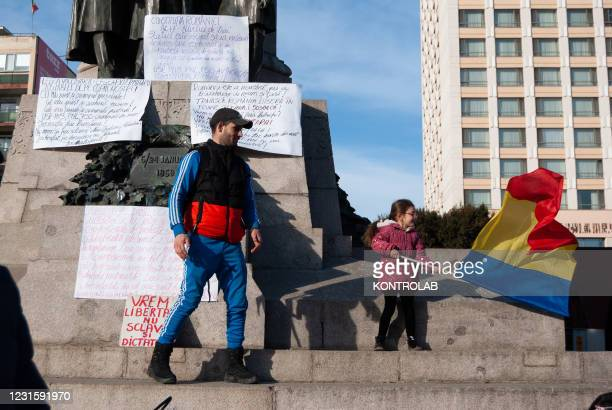 Child plays with a Romanian flag on the statue of Alexandru Ioan Cuza in Union Square during a demonstration against vaccinations, the use of masks...