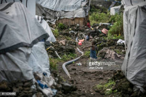 A child plays with a twig next to a water pipe on a lavafilled ground at a Mugunga IDP camp on June 24 2014 in Goma Democratic Republic of Congo...