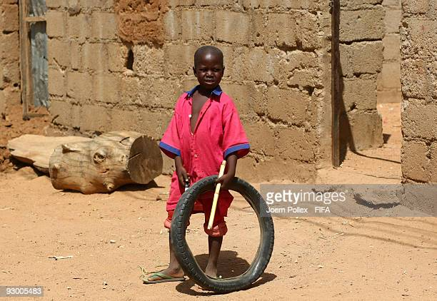 A child plays with a tyre and stick in the street on November 07 2009 in Bauchi Nigeria