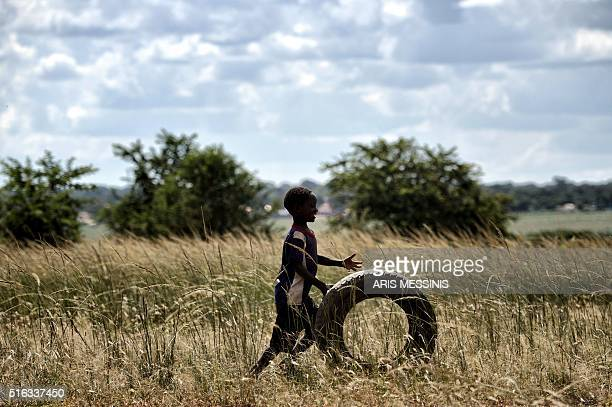 A child plays with a wheel at a field at the outskirts of Lilongwe on March 11 2016 / AFP / ARIS MESSINIS