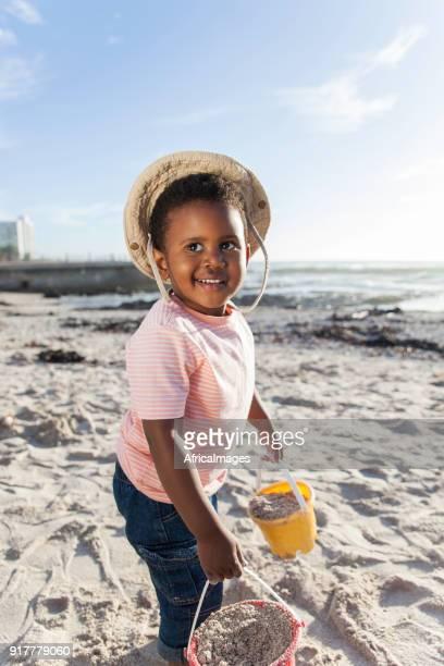 enfant joue avec des seaux de sable sur la plage. - pantalon noir photos et images de collection
