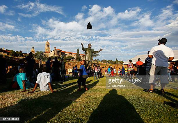 A child plays with his hat near the statue of Former South African President Nelson Mandela that was unveiled at the Union Buildings on December 16...