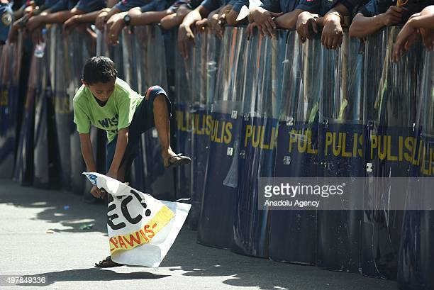 A child plays with one of the activists streamers in front of a wall of anti riot police officers barricading protesters from various groups as they...